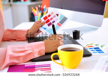 Artist drawing on graphic tablet in office - stock photo