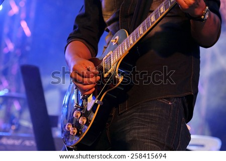 artist Guitarist hand play guitar on concert stage with blue light, Practicing in playing guitar. man playing guitar,rock and roll, electricity guitar background, song entertainment, music instrument.