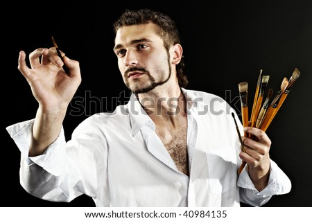 artist in a white shirt on a black background with a brush. contrast shot - stock photo