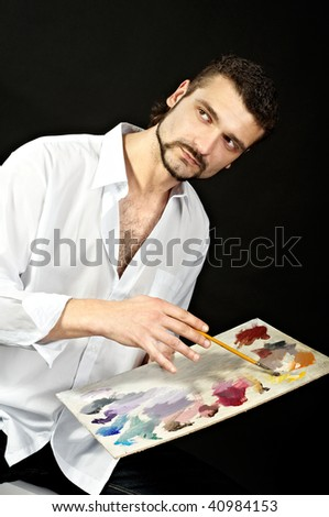 artist in a white shirt on a black background with a brush. Makes the outline of the palette. Look into the camera - stock photo