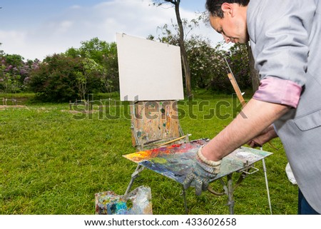 Artist Looking To His Palette And Choosing Brushes To Start Painting Oudoor - stock photo