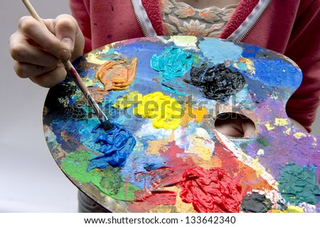 Artist mixes oil paints on pallet with various colors - stock photo
