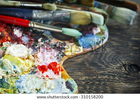 Artist paint brushes and palette on wooden background. Selective focus - stock photo