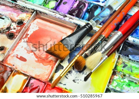 Artist paint brushes on watercolor palette.