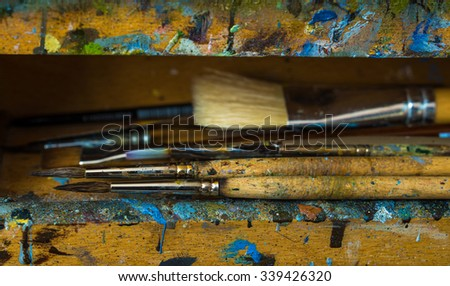 Artist paintbrushes closeup on old wooden easel with blobs of paint - stock photo