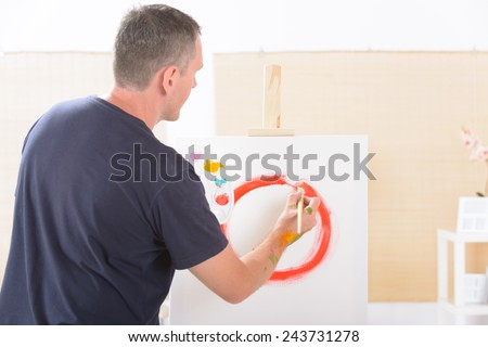 Artist painting holding paintbrush with artist palette, canvas on easel in a background - stock photo