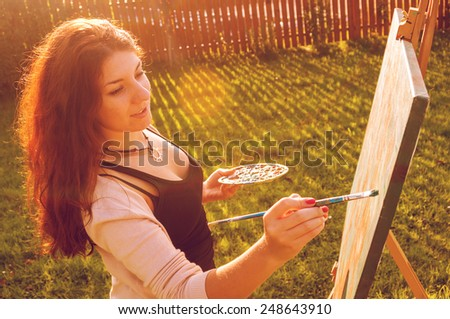 Artist painting in the sun - stock photo