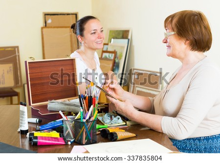 Artist  painting  portrait of woman at workshop - stock photo