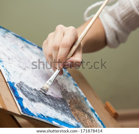 artist paints oil painting on canvas - stock photo