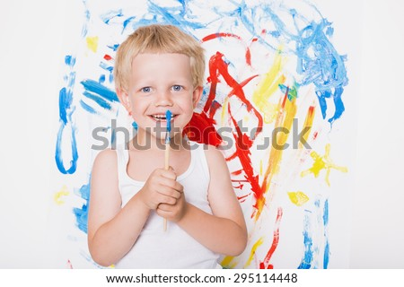 Artist preschool boy painting brush watercolors on a easel. School. Education. Creativity. Studio portrait over white background - stock photo