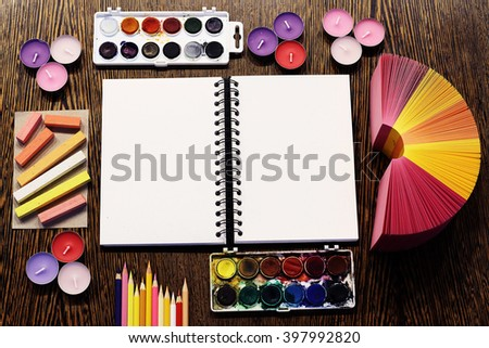 Artist's empty sketchbook/notepad surrounded by set of artistic tools. Pastel toning - yellow, orange, ping, purple and violet. Flat-lay/close up shot from above. - stock photo