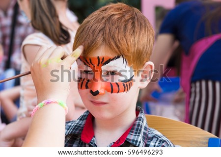 Artist's hand draws face painting to little boy. Child with funny face art. Painter makes tiger eyes on boy's face. Children holiday, event, birthday party, entertainment.