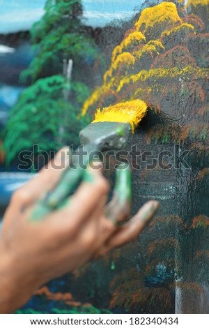 Artist's hand with a brush at work - stock photo