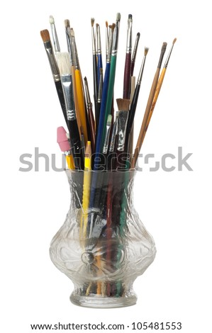 Artist's paint brushes and pencils fill a transparent glass vase isolated on white