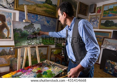 Artist working in a gallery or studio selecting a particular hue from a colorful palette of blended oil paints as he works on a painting on an easel - stock photo