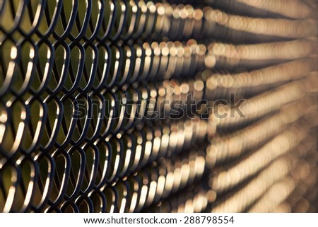 Artistic abstract view of black chain link fence in  late afternoon sunlight. Horizontal background. Fence chain links are in focus on the left side, fade to abstract out of focus shapes to right. - stock photo