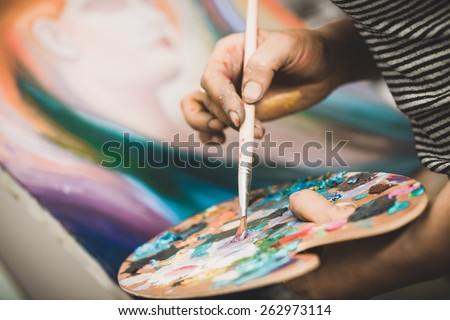 Artistic. artist paints a picture of oil paint brush in hand with palette closeup - stock photo