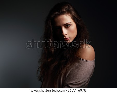Artistic beautiful woman with long hair looking sexy. Shadow on half face. Closeup art portrait - stock photo