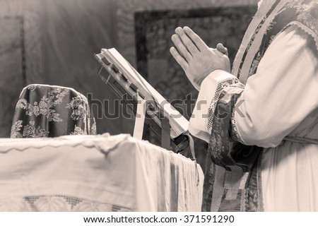Artistic black and white dark vintage edit of a priest saying the extraordinary form, traditional latin tridentine rite Catholic mass. A detail.  - stock photo