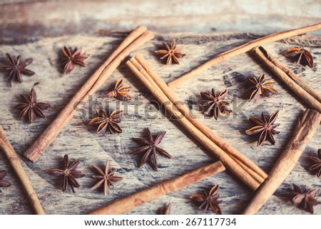 Artistic closeup of cinnamon and star anise seeds on a wooden background. Sunny still life photo.   - stock photo