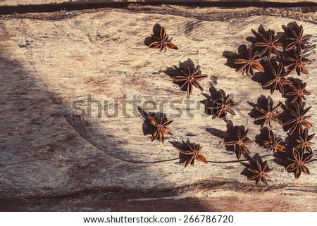 Artistic closeup of star anise seeds on a wooden background. Sunny still life photo.   - stock photo