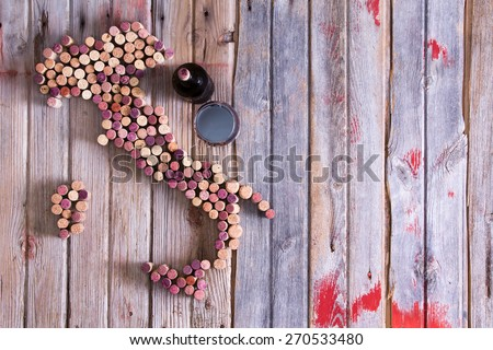 Artistic conceptual map of Italy, Sardinia and Sicily made of old red and white wine bottle corks on an old rustic wooden table with a glass and bottle of red wine alongside - stock photo