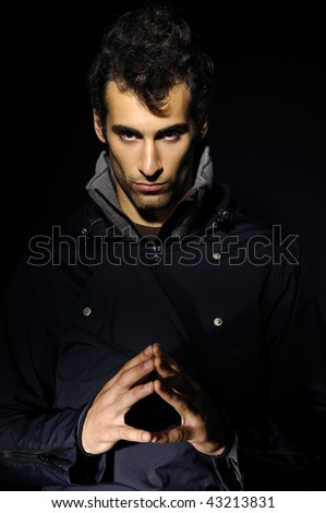 Artistic dark portrait of handsome man with blue eyes - stock photo
