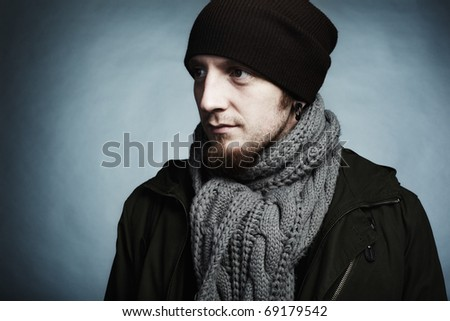 Artistic dark portrait of the young beautiful man in a cap and a dark jacket