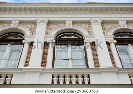 Artistic decorations on old building facade above three windows -  architectural detail.