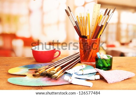 Artistic equipment: paint, brushes and art palette - stock photo