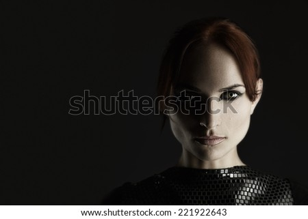 Artistic fashion portrait of young redhead woman. Shadow on half of face