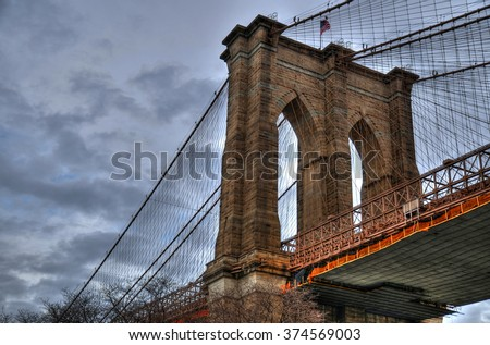 Artistic HDR image of the Brooklyn Bridge on a cloudy day (close up upward view image)