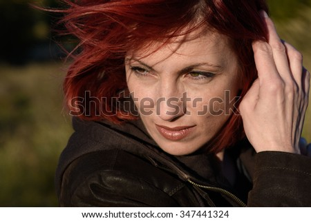 artistic head shoot of beautiful melancholic woman looking away over the shoulder holding her hair outdoor  - stock photo