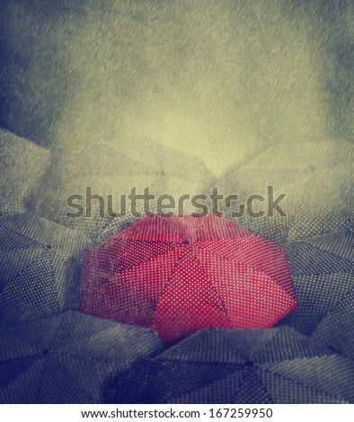 Artistic image of red umbrella standing out from the crowd - stock photo