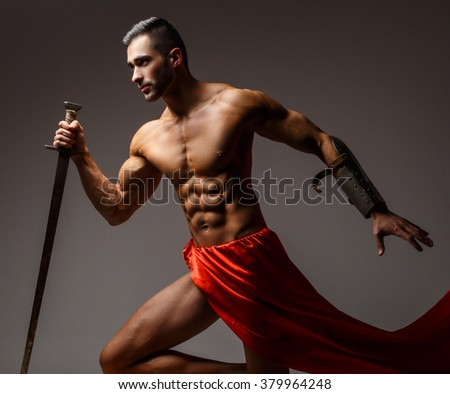Artistic image with naked muscular man in a red fluttering dress. - stock photo