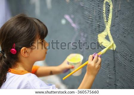 Artistic kid painting mural - stock photo