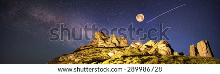 Artistic lighting unreal mountain scenery while rock climbing in the wild mountains provides a unique fantastic effect unearthly planets with fabulous landscapes of Mars. Shooting stars. - stock photo