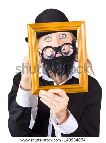 Artistic man looking through empty picture frame. Artwork valuation concept - stock photo