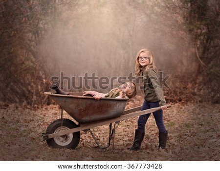 artistic moody outdoor portrait of two blond girls playing with a wheel barrow in a woods - stock photo