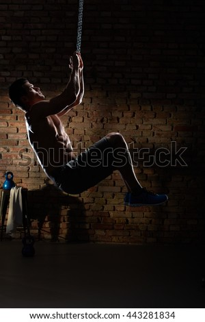 Artistic photo of muscular man doing crossfit workout with chain, indoors. - stock photo