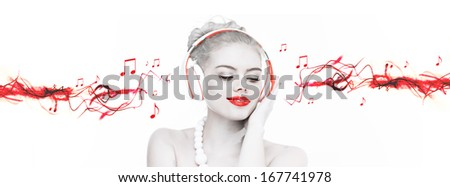 Artistic portrait of a beautiful woman wearing headphones listening to music with selective red colour and streaming music - stock photo