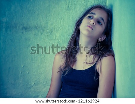 Artistic portrait of a sad hispanic girl sitting next to a dirty wall toned in blue shades - stock photo