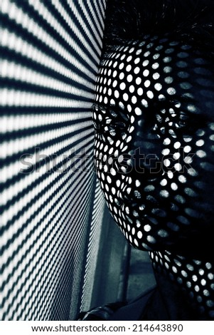 Artistic portrait of a young woman with polka dots shadows on her face - stock photo