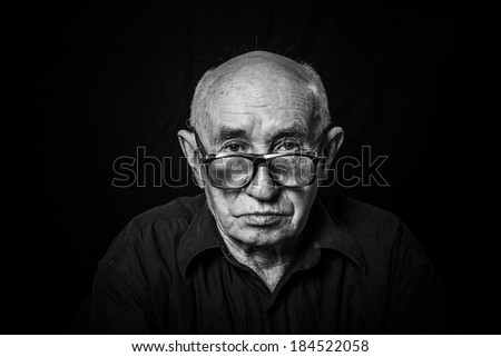 Artistic portrait of an old man with glasses - stock photo