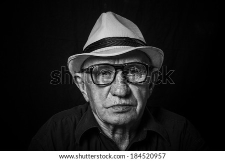 Artistic portrait of an old man with glasses and hat