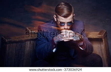 Artistic portrait of bearded man in sunglasses and with tattooes on arms. - stock photo