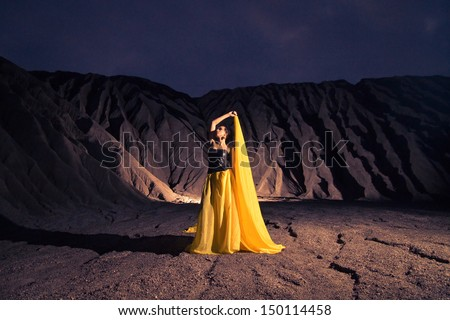 Artistic portrait of brunette model with long yellow skirt. in front of mountains - stock photo
