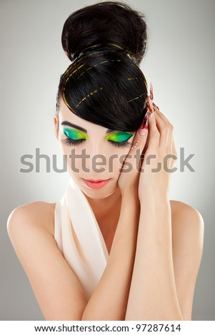 Artistic portrait of dreamy young brunette with beautiful makeup and finger nails - stock photo