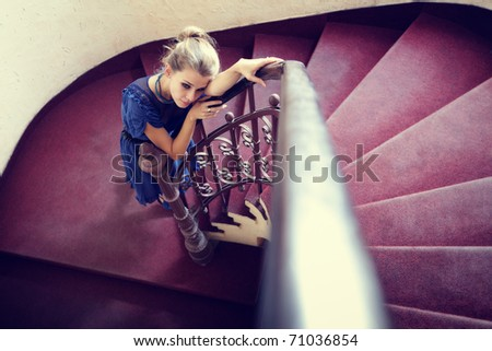 Artistic portrait of elegant woman on circular stairway - stock photo