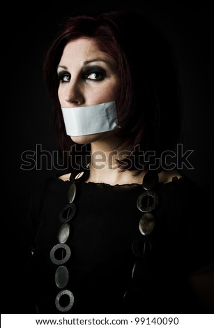 Artistic portrait of woman with tape over her mouth, signifying freedom of speech - stock photo